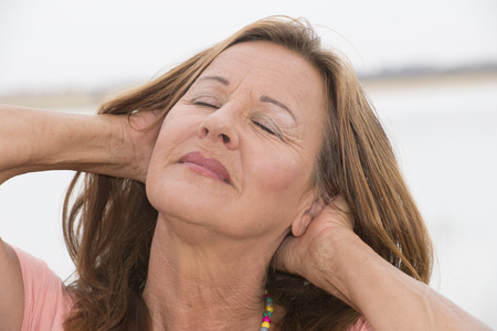 laid back: Portrait attractive mature woman posing happy smiling with hands behind head and closed eyes, relaxed meditating