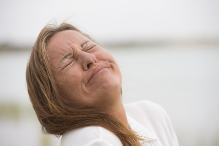 Portrait mature woman with sad, stressed, painful facial expression, crying with closed eyes outdoor