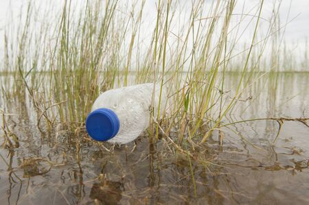Empty plastic bottle illegal dumped and disposed, floating as garbage in water of river or lake between grass photo