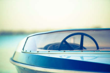 speedboat: Detail of moored or anchored speed motor boat with steering wheel, blurred background of lake or ocean at sunset, copy space.