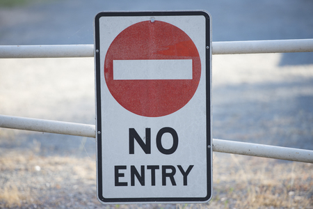 trespassing: No entry sign on gate to restricted area of property in blurred background Stock Photo