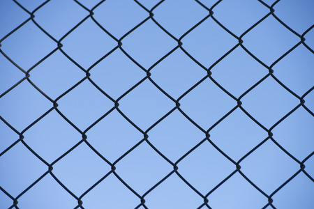 detain: Security mesh fence, with texture on blue sky outdoor background Stock Photo