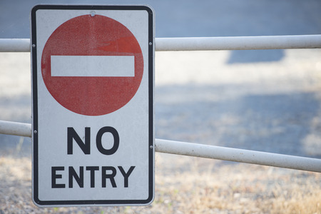 restricted area: No entry sign on boom gate to restricted area of property in blurred background