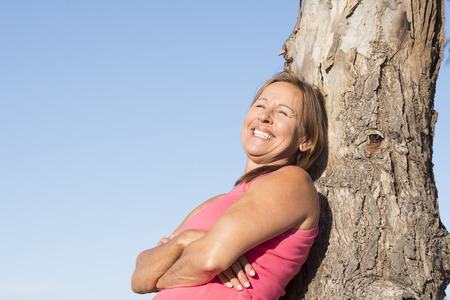 laid back: Portrait attractive mature woman leaning against tree outdoor, relaxed and laid back, happy joyful smiling, with blue sky as background and copy space.