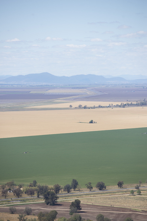 south space: Aerial view of agricultural farmland in New South Wales, Australia, with fields and meadows of wheat  and crop, mountain range in blurred background and copy space.