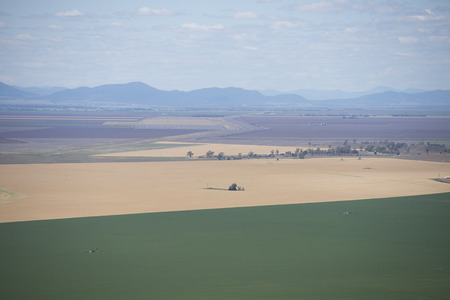 south space: Aerial view of agricultural farmland in New South Wales, Australia, with fields and meadows of crop and wheat, mountain range in blurred background and copy space. Stock Photo