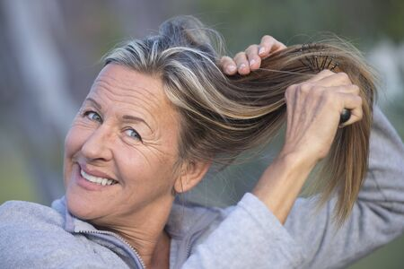 Portrait attractive mature woman outdoor, combing hair with brush with blurred background. Stock Photo