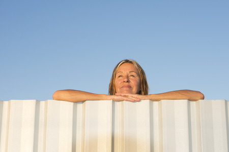 laid back: Portrait of attractive mature woman leaning relaxed and laid back on metal fence with chin resting on hands, with blue sky as background and copy space. Stock Photo