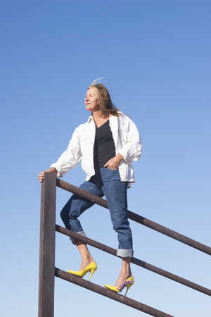 laid back: Portrait attractive mature woman standing confident in high heel shoes on top of metal fence, laid back and relaxed, friendly smiling, with blue sky as background and copy space.
