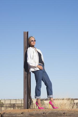campagne rural: Portrait s�duisante femme d'�ge m�r, debout en plein air d�tendu confiants dans les chaussures � talons hauts, avec des paysages ruraux et de ciel bleu en arri�re-plan et de l'espace de copie. Banque d'images
