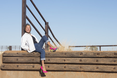 laid back: Portrait attractive mature woman posing relaxed sitting at metal fence in rural country area, wearing pink high heel shoes, with blue sky as background and copy space.