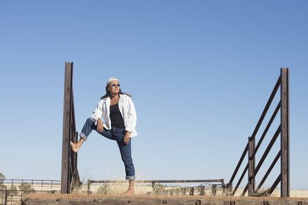 bare feet: Portrait of attractive mature woman, standing confident and leisure bare feet outdoor, leaning against metal fence, wearing jeans, jacket, sunglasses and hat, with horizon and blue sky as copy space and background.