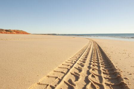 Off road car tyre track on sandy beach, with ocean and blue sky as blurred background and copy space.