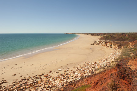 western australia: Beautiful Pristine remote beach with rugged coastline close to Broome in Western Australia, with turqoise colored ocean and blue summer sky as background and copy space. Stock Photo