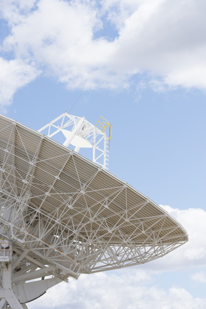 satellite space: Telescope dishes for astronomical scientific research standing in outback Australia, searching the sky for galaxies, stars and planets in the universe, with blue sky and clouds as background and copy space. Stock Photo