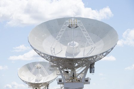 Two telescope dishes for astronomical scientific research standing in outback Australia, searching the universe for galaxies, stars and planets, with blue sky and clouds as background and copy space.