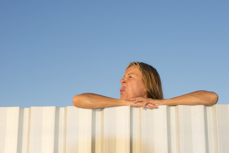 disrespectful: Portrait of attractive mature woman leaning relaxed on metal fence while showing with naughty facial expression her tongue, with blue sky as background and copy space. Stock Photo