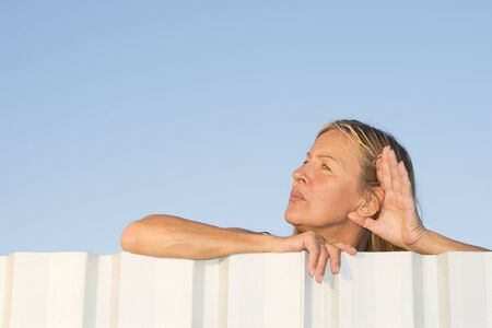 laid back: Portrait of attractive mature woman listening curious to noise outdoor, while leaning over metal fence with one hand to ear, with blue sky as background and copy space.