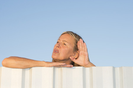 prying: Portrait of attractive mature woman listening curious to noise or sound outdoor, while leaning over metal fence with one hand to ear, with blue sky as background and copy space.