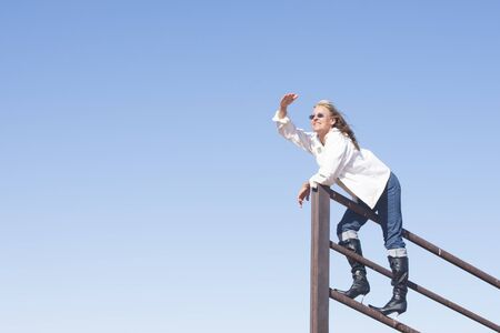 laid back: Portrait attractive happy laid back smiling mature woman standing confident on lookout, wearing high heel boots, with blue sky as background and copy space. Stock Photo