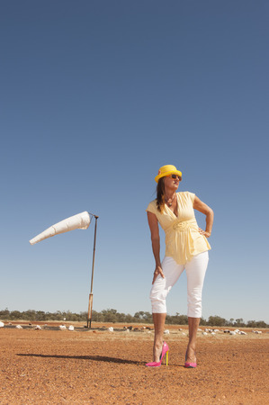 outback australia: Portrait beautiful mature traveling woman standing alone on remote airfield of rural airport in outback Australia, posing in high heel shoes, with blue sky as background and copy space.