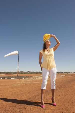 outback australia: Portrait attractive mature traveling woman standing alone on remote airfield of rural airport in outback Australia, wearing high heel shoes, with blue sky as background and copy space. Stock Photo