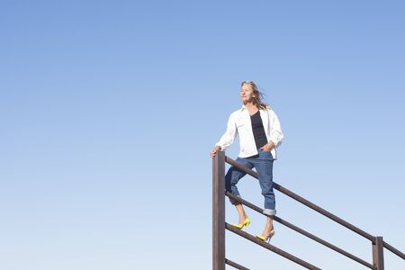 laid back: Portrait confident and attractive mature woman standing laid back and relaxed on top of metal fence in high heel shoes, lookout position, with blue sky as background and copy space.