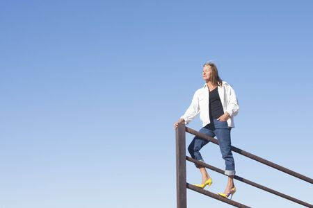 laid back: Portrait beautiful mature woman standing confident in high heel shoes on top of metal fence, laid back and relaxed, friendly smiling, with blue sky as background and copy space.