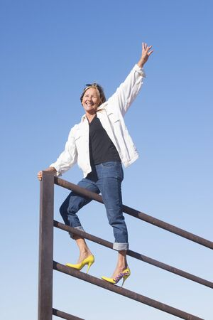 high spirits: Portrait attractive mature woman standing in high heel shoes and winning pose on top of metal fence, happy smiling, arms up and joyful, with blue sky as background and copy space.