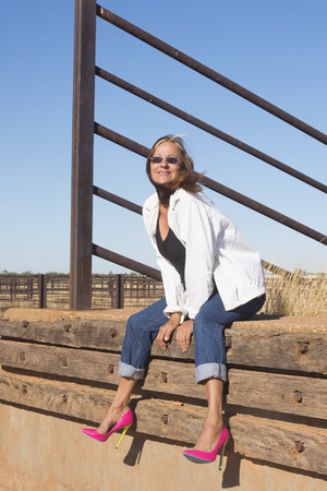 laid back: Portrait attractive mature woman sitting happy and confident outdoor in rural country area, wearing high heel shoes and sunglasses, with blue sky as copy space.