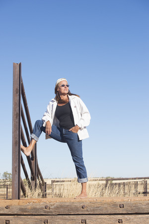 laid back: Portrait of attractive mature woman, standing confident and laid back bare feet outdoor, leaning against metal fence, wearing jeans, jacket, sunglasses and hat, with horizon and blue sky as copy space and background. Stock Photo