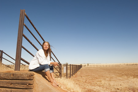 farming area: Portrait attractive mature woman sitting relaxed at metal fence line in rural farming area in outback Australia, with dry arid agricultural country and blue sky as background and copyspace.