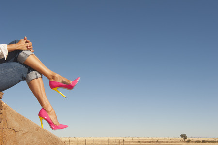 Attractive crosslegged Female legs wearing sexy colourful pink high heel shoes sitting relaxed outdoor, with field and blue sky as background and copy space.