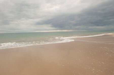 turqoise: Open seascape woth turqoise shimmering water of ocean and dark storm clouds hanging over the sea, copy space. Stock Photo