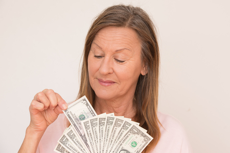 woman holding money: Portrait happy attractive mature woman presenting US dollar money, isolated, bright background.