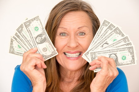 woman holding money: Portrait attractive mature woman presenting happy joyful relaxed us dollar notes, isolated, bright background. Stock Photo
