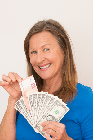 woman smiling: Portrait happy smiling attractive mature woman presenting Euro and US dollar currency, isolated, bright background.