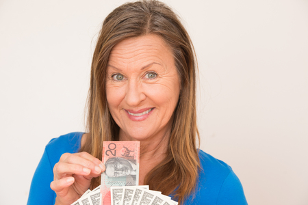 australian dollar notes: Portrait attractive mature woman holding relaxed smiling Australian and US dollar notes, isolated, bright background. Stock Photo