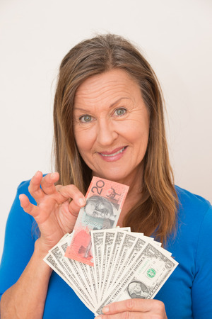australian dollar notes: Portrait attractive mature woman presenting relaxed smiling Australian and  US dollar notes, isolated, bright background. Stock Photo