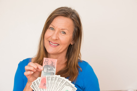 australian dollar notes: Portrait attractive mature woman holding relaxed Australian and  US dollar notes, isolated, bright background.