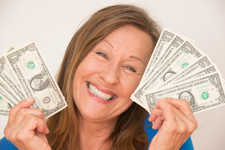 Portrait relaxed attractive mature woman holding happy smiling us dollar notes, isolated, bright background. photo