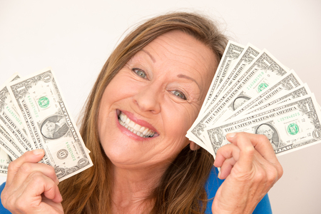 Portrait attractive mature woman holding happy relaxed with closed eyes us dollar notes, isolated, bright background. photo