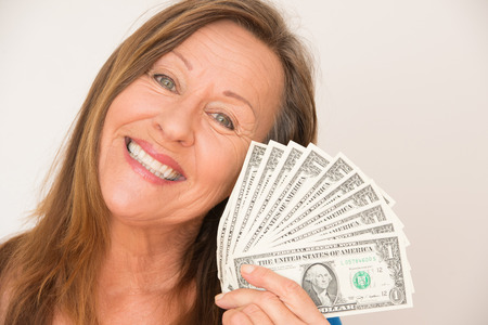 Portrait happy attractive mature woman holding us dollar notes, bright background. photo