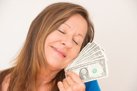 Portrait relaxed attractive mature woman holding happy with closed eyes us dollar notes, isolated, bright background. photo