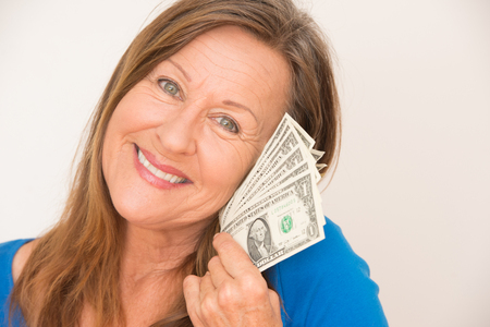 Portrait attractive mature woman holding joyful relaxed with us dollar notes, isolated, bright background. photo