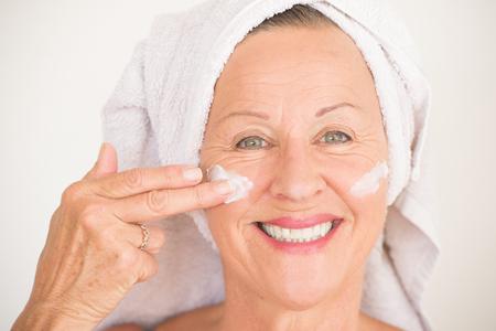 Portret aantrekkelijke rijpe vrouw met een handdoek en beschermende huidverzorging crème en vochtinbrengende lotion op gelukkig lachend gezicht, lichte achtergrond.