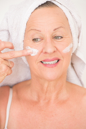 moisturiser: Portrait attractive senior woman with towel and protective skin care creme and moisturiser lotion on happy smiling face, bright background.