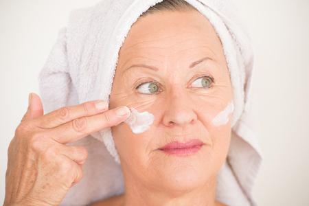 Portret vriendelijke aantrekkelijke rijpe vrouw met een handdoek en beschermende huidverzorging crème en vochtinbrengende lotion op gelukkig lachend gezicht, heldere achtergrond. Stockfoto