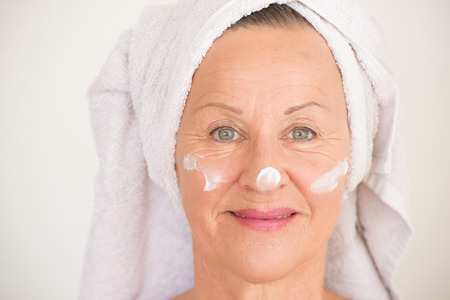 moisturiser: Portrait beautiful mature woman with towel and protective skin care creme and moisturiser lotion on happy smiling face, bright background.