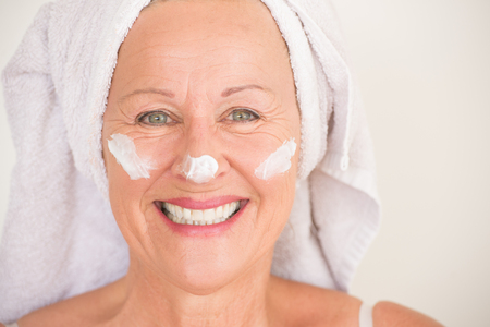 moisturiser: Portrait joyful attractive mature woman with towel and protective skin care creme and moisturiser lotion on happy laughing face, bright background.